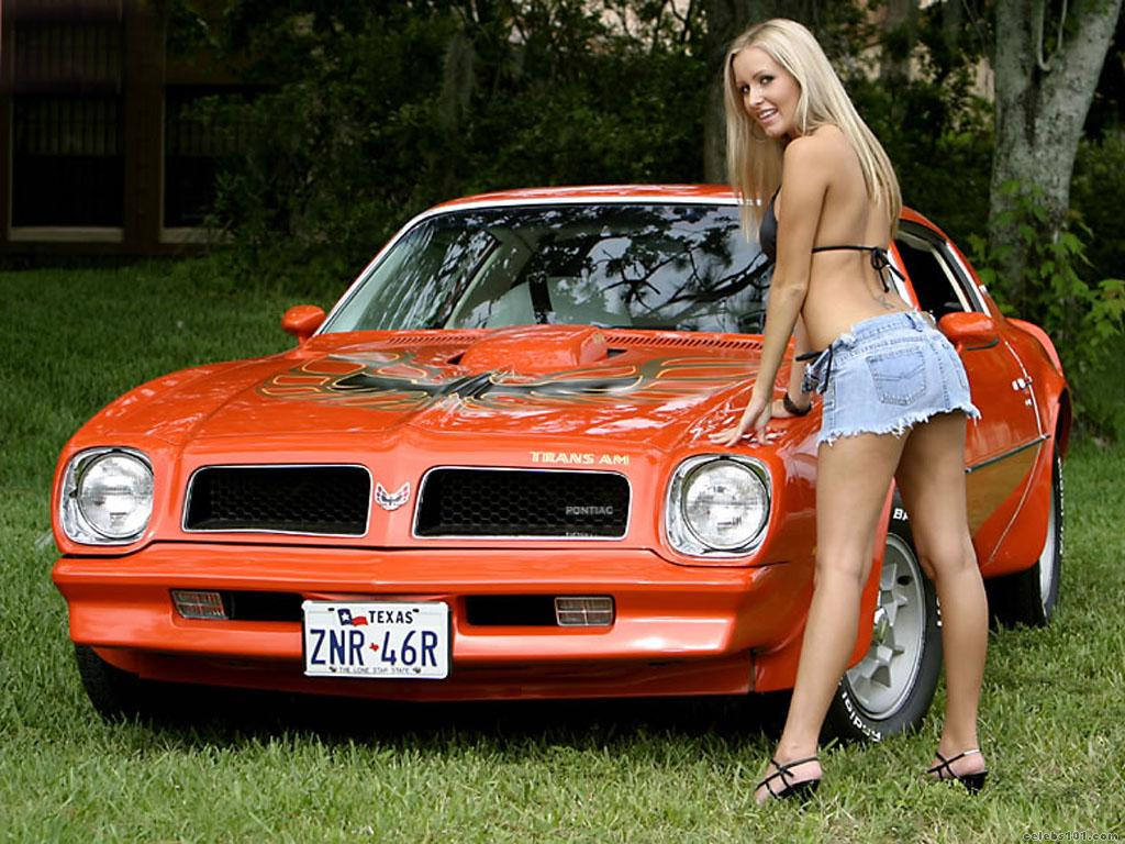 naked woman posing with a trans am